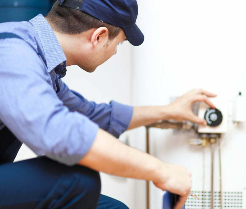 Electrician or Plumber adjusting a water heater gauge